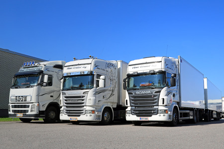 TURKU, FINLAND - SEPTEMBER 13, 2014: Fleet of white Scania R series and Volvo FH trucks by a warehouse. According to Statistic Finland, a total of 67 million tonnes of goods were transported by lorries in Q2 of 2014. Редакционное