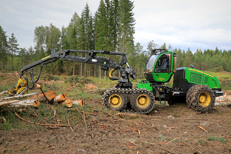 deere: TAMMELA, FINLAND - AUGUST 31, 2014: John Deere 1270E wheeled harvester with chains at a forest logging site. The The 1270E was introduced in 1996 and it has a large 9.0-liter engine and CH7 Harvester boom. Editorial