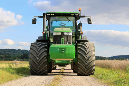 SALO, FINLAND - SEPTEMBER 6, 2014: John Deere 7280R agricultural tractor on a rural road by oilseed fields. The 7280R has 9.0 l DieselOnly PowerTech PVX engine.