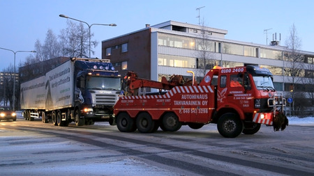 towed: SALO, FINLAND - DECEMBER 27, 2014: Truck and full trailer is being towed by a heavy duty tow truck. The rapidly changing temperatures and weather conditions can be challenging for heavy duty vehicles in winter.