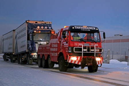 SALO, FINLAND - DECEMBER 27, 2014: Truck and full trailer is being towed by a heavy duty tow truck. The rapidly changing temperatures and weather conditions can be challenging for heavy duty vehicles in winter.