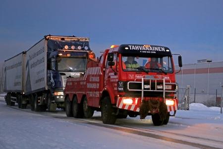 Salo, Finlandia - 27 de diciembre 2014: Camión y remolque completo está siendo remolcado por una grúa de servicio pesado. Las temperaturas rápidamente cambiantes y las condiciones meteorológicas pueden ser un reto para los vehículos pesados ??en invierno. Editorial
