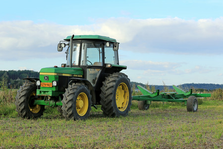 deere: SALO, FINLAND - SEPTEMBER 6, 2014: John Deere 2850 utility tractor and agricultural trailer. The model 2850 was manufactured between 1986-1994 in Germany and Argentina.