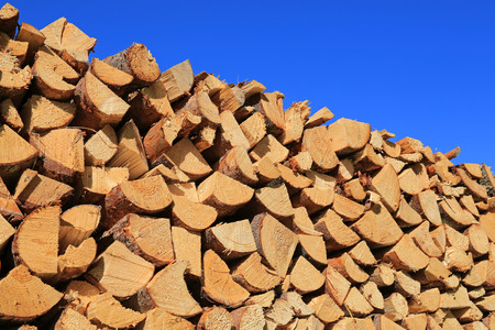 Cut, chopped and stacked up dry firewood against clear blue sky. photo