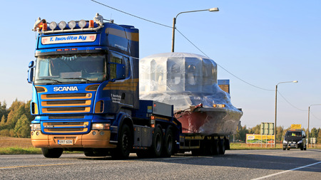 accompanied: LUVIA, FINLAND - SEPTEMBER 19, 2014: Scania R500 hauls a wide load accompanied by an escort car. If the width of the transport exceeds 3.5 metres, the maximum permissible speed on Finnish roads is 60 kmh.