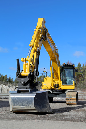 locomotion: RAISIO, FINLAND - MARCH 22, 2014: Komatsu crawler excavator on a yard. A crawler excavator or crawling digger  is a vehicle designed to dig or move large objects, and is classified by its mode of locomotion.