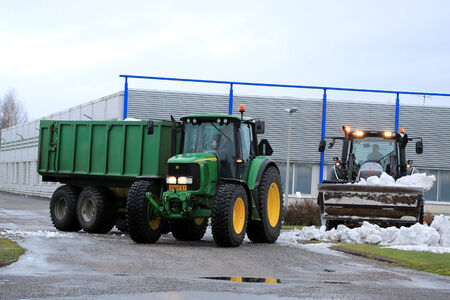 deere: SALO, FINLAND - JANUARY 18, 2015: Unidentified workmen removing snow with Valtra and John Deere tractos in Salo, Finland. The snow is transported from streets and properties to a local snow dump site.