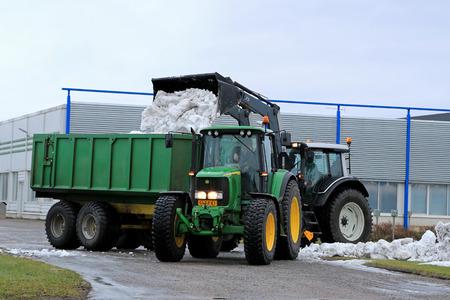 cargador frontal: Salo, Finlandia - 18 de enero de 2015: los hombres no identificados descarga de nieve con cargador frontal en un tractor remolque John Deere 6620 en Salo, Finlandia. La nieve es transportado desde las calles y propiedades a un vertedero local de nieve.
