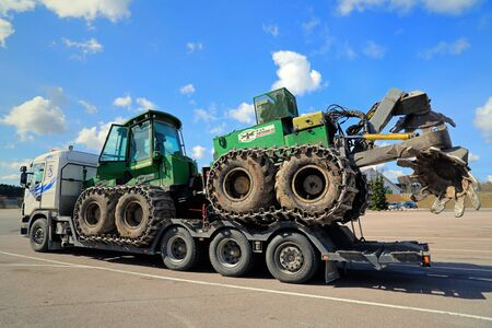 PAIMIO, FINLAND - MAY 3, 2014: John Deere forestry harvester with a double disk forest plough on a truck trailer. Before planting trees, dry types of forest floor can sometimes be tilled.