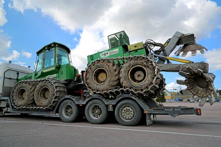 deere: PAIMIO, FINLAND - MAY 3, 2014: John Deere forestry harvester with a double disk forest plough on a truck trailer. Before planting trees, dry types of forest floor can sometimes be tilled.