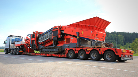 SALO, FINLAND - AUGUST 18, 2013: Volvo FH hauls a Terex Finlay tracked mobile jaw crusher on double drop deck trailer. Terex jaw crushers are used for the reduction and sizing of aggregates for construction materials..