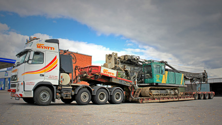 oversize load: TURKU, FINLAND - SEPTEMBER 15, 2013: Volvo FH16 hauls a pile driver on a double drop deck trailer. A pile driver is a mechanical device used to drive piles or poles into soil to provide foundation support for buildings.