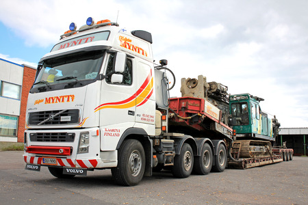 oversize load: TURKU, FINLAND - SEPTEMBER 15, 2013: Volvo FH16 hauls a pile driver on a double drop deck trailer. A pile driver is a mechanical device used to drive piles (poles) into soil to provide foundation support for buildings.