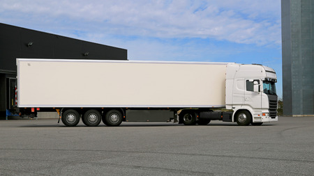 distribution box: White semi trailer truck on a warehouse yard ready to transport cargo. Stock Photo