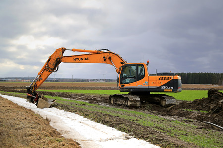 cummins: AURA, FINLAND - MARCH 1, 2015: Hyundai Robex 210LC-9 Crawler Excavator on a field. The R210LC-9 has  horizontal reach of 10,9 m and dregding depth of 7,7 m. Editorial
