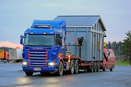 FORSSA, FINLAND - DECEMBER 7, 2014: Scania R500 hauls an exceptional load at dusktime. In several Finnish regions, transport of abnormal loads is not permitted during rush hours.