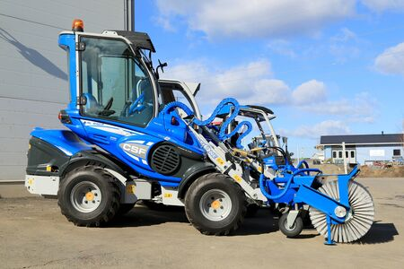 TURKU, FINLAND - MARCH 21, 2015: Multione compact miniloader with a brush attachment outside on a yard. Multione includes different models and over 170 attachments which can be replaced. Editorial