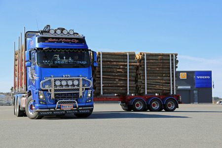 compared: FORSSA, FINLAND - APRIL 11, 2015: Volvo FH16 700 logging combination vehicle turns in a small space compared to its length.
