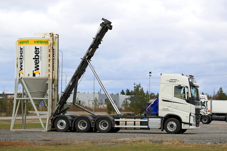 weber: LIETO, FINLAND - APRIL 19, 2015: Volvo FH picks up Weber Saint-Gobain silo of construction materials. Saint-Gobain celebrates 350 years in 2015.