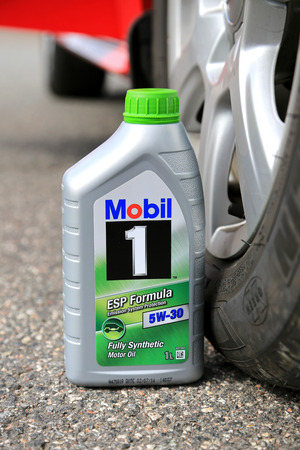 motor oil: LOIMAA, FINLAND - APRIL 25, 2015: A container of Mobil1 5W-30 fully synthetic Motor oil against car tyre. Multiweight oils such as 5W-30 have polymers added to the oil.