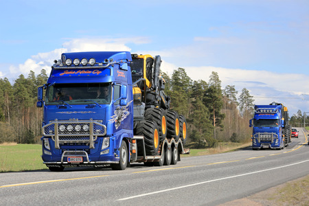 haul: KAARINA, FINLAND - MAY 2, 2014: Two Volvo FH trucks haul Ponsse forest machinery along highway 40. According to recent Q1 2015, Ponsses net sales amounted to EUR 91.2 million.