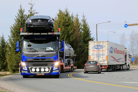 estimates: SALO, FINLAND - MAY 1, 2015: Volvo FM carrier hauls a load of new cars. The Finnish automotive industry estimates that a total of 109,000 new passenger cars will be sold in Finland in 2015.