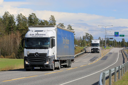 time sensitive: KAARINA, FINLAND - MAY 3, 2015: Two Mercedes-Benz Actros trucks of Kim Johansen Transport Group. The Danish company has focus on transport of time sensitive goods within Europe.