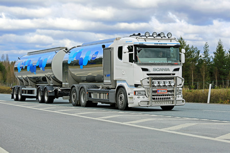 hauling tractor: SALO, FINLAND - MAY 2, 2015: New Scania R500 tank truck transports Valio milk along motorway. The usual temperature of transported milk is 3 degrees Celsius.