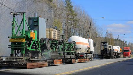 asphalting: KAARINA, FINLAND - MAY 14, 2015: Asphalting machinery at roadworks. Hot mix asphalt concrete is produced by heating the asphalt binder to decrease its viscosity.