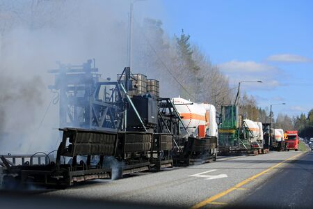 asphalting: KAARINA, FINLAND - MAY 14, 2015: Asphalting at roadworks. Hot mix asphalt concrete is produced by heating the asphalt binder to decrease its viscosity.