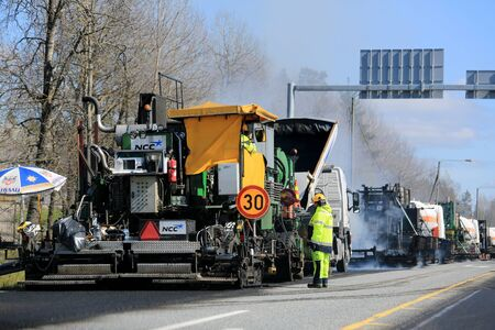 viscosity: KAARINA, FINLAND - MAY 14, 2015: Machine laying asphalt concrete and unidentified workmen at road works. Hot mix asphalt concrete is produced by heating the asphalt binder to decrease its viscosity.