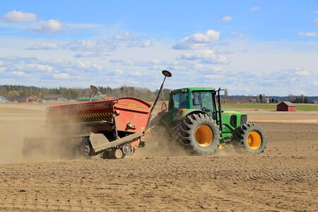 deere: LOIMAA, FINLAND - APRIL 25, 2015: John Deere 6620 Agricultural Tractor and VM Direct Seed Drill on a field at spring. Real Direct Seeding has advantages to soil structure and water management. Editorial