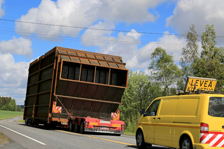 exceeds: SALO, FINLAND - MAY 31, 2015: Escort cars accompany an exceptional load transport along highway. On Finnish roads at least one escort vehicle is necessary, if the load exceeds 3,5 m in width.