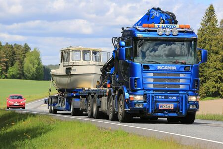SALO, FINLAND – MAY 31, 2015: Scania 124 hauls a recreational boat on a drop deck trailer. The Finnish boating season gets busy at the beginning of June.