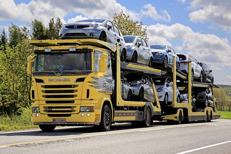 Salo, Finlandia - 31 de mayo 2015: El amarillo Scania R500 camión transporta una carga de coches nuevos. La industria del automóvil finlandés estima que un total de 109.000 turismos nuevos se venderá en Finlandia en 2015.