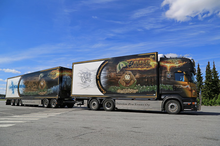 reefer: FORSSA, FINLAND - MAY 31, 2014: Scania V8 temperature controlled combination vehicle leaves truck stop. Refrigerated trucks can haul a variety of goods that require a climate-controlled handling. Editorial