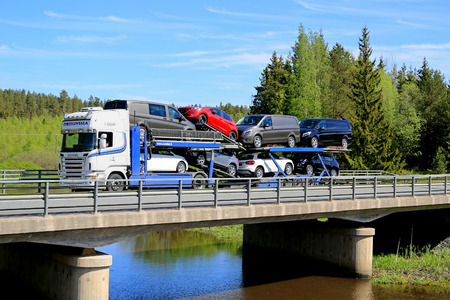 FORSSA, FINLAND - MAY 30, 2015: White Scania R480 auto carrier hauls a load of new cars along bridge. The Finnish automotive industry estimates that a total of 109,000 new passenger cars will be sold in Finland in 2015.