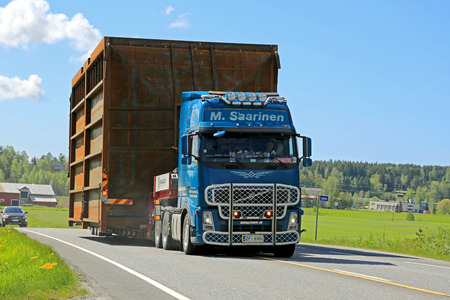 exceeds: SALO, FINLAND - MAY 31, 2015: Volvo FH truck hauls a wide load along highway accompanied by escort cars. On Finnish roads at least one escort vehicle is necessary, if the load exceeds 3,5 m in width.