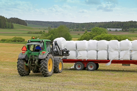 agriculture machinery: PAIMIO, FINLAND - JUNE 7, 2015: Unidentified farmer stacks up silage with Quicke Q55 loader and John Deere 6330 tractor. Wrapping bales has been widely adopted in over 50 countries worldwide.