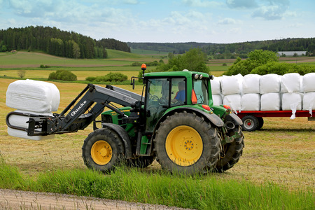 PAIMIO, FINLAND - JUNE 7, 2015: Unidentified farmer stacks up silage with Quicke Q55 loader and John Deere 6330 tractor. Wrapping bales has been widely adopted in over 50 countries worldwide.
