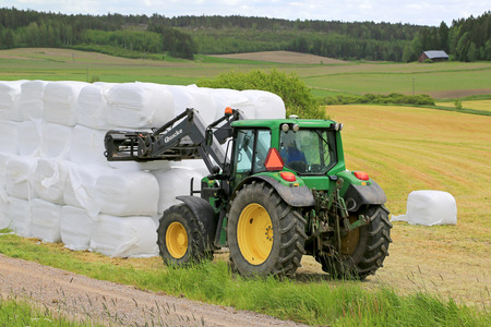 deere: PAIMIO, FINLAND - JUNE 7, 2015: Unidentified farmer stacks up silage with Quicke Q55 loader and John Deere 6330 tractor. Wrapping bales has been widely adopted in over 50 countries worldwide.