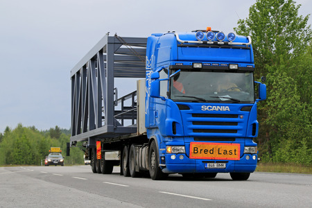 escort: KONGINKANGAS, FINLAND - JUNE 20, 2015: Scania truck hauls a wide load accompanied by an escort car. The abnormal transport permit is required, if any dimension of the transport exceeds the free dimension limits.