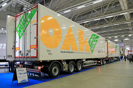 tonne: HELSINKI, FINLAND - JUNE 11, 2015:  The OAK Green Double 88 tonne combination vehicle presented at Logistics Transport 2015. The vehicle length is 32 m and it consists of  a Scania R730 tractor and two NTM semi trailers. Editorial