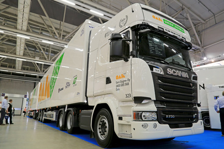 tonne: HELSINKI, FINLAND - JUNE 11, 2015:  The OAK Green Double 88 tonne combination vehicle presented at Logistics Transport 2015. The vehicle length is 32 m and it consists of a Scania R730 tractor and two NTM semi trailers.