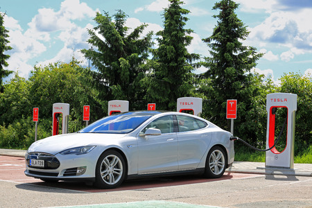 charging: PAIMIO, FINLAND - MAY 14, 2015: Tesla Model S is being charged at Tesla Supercharger station. Charging the battery from 10 to 80 percent takes about 40 minutes.
