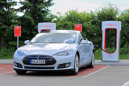 supercharger: PAIMIO, FINLAND - MAY 14, 2015: Tesla Model S being charged at Tesla Supercharger station. Charging the battery from 10 to 80 percent takes about 40 minutes.