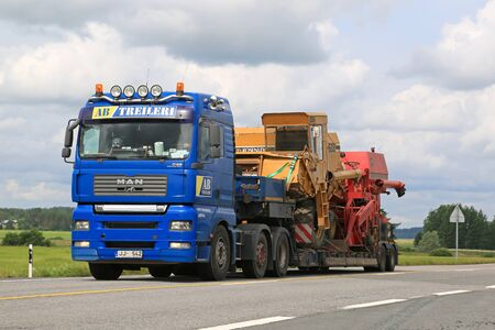abnormal: JOKIOINEN, FINLAND - JULY 18, 2015: MAN truck hauls two combine harvesters on low floor trailer. The abnormal transport permit is required, if any dimension of the transport exceeds the free dimension limits. Editorial