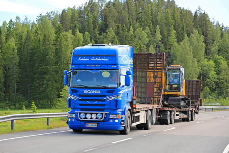 v8: SALO, FINLAND - JUNE 12, 2015: Blue Scania V8 truck hauls New Holland crawler excavator.  New Holland Construction produces thirteen product families.
