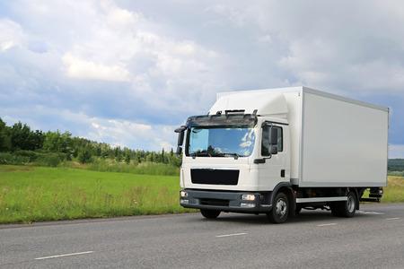 ciężarówka: Biały samochód dostawczy ruchu handlowych na drodze. Kopiowanie miejsca na lewo. Zdjęcie Seryjne