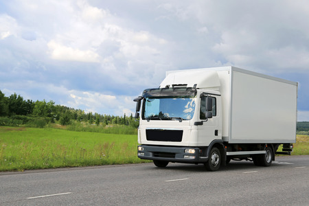White commercial delivery truck moving on the road. Copy space on the left.